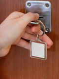 Closing house door by key with blank keychain Stock Photography