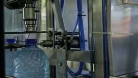 Closing plastic bottles with water on conveyor belt in modern company indoor. stock video footage