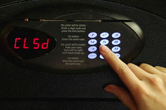 Closing of safe. Closeup of a female hand using the code keypad on a metal safe to close it Stock Photography