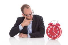 Closing time at four o'clock: isolated businessman looking pensi Royalty Free Stock Photography
