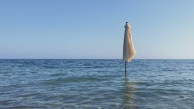 Closing umbrella in the sea. Closing umbrella stand in the sea against blue sky. Blue water moves from light wind and creates a waves. Beautiful sea nature stock video