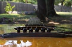 Closuep de la guitarra que mira abajo de las secuencias del cuerpo Imagen de archivo libre de regalías