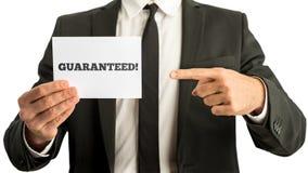 Closuep wskazuje biała karta z gwarancją biznesmen zdjęcia royalty free