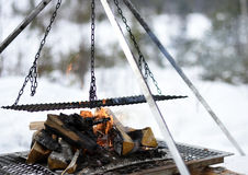 Closup of a construction for cooking in nature in winter. On a burning fire, picture from the North of Sweden Royalty Free Stock Photography