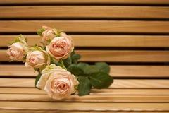 Closup do ramalhete da rosa do rosa em um banco de madeira Fotografia de Stock Royalty Free