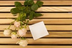 Closup för rosa färgrosbukett och klistermärkeanmärkning på en träbänk arkivbild
