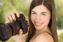 Closup portrait of woman photographer taking a photo with camera Stock Photo