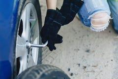 closup räcker demontering av hjulet från bilen royaltyfria foton