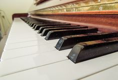 Closup of a wooden piano with two black keys in focus stock photography