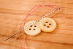 Sewing needle with thread and cloth buttons on wooden background Royalty Free Stock Photography