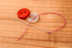Cloth buttons and sewing needle with red thread on wooden table. Cloth buttons and sewing needle with red thread on wooden desk. Selective focus. Close up Royalty Free Stock Photos