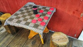 Cloth checker board. Outdoors with wood stools and red wall. royalty free stock photo