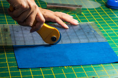 Cloth cutting process. Woman's hands using rotary cutter for her patchwork Royalty Free Stock Photos