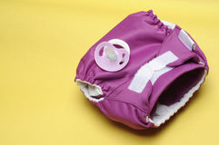 Cloth Diaper with Dummy on Yellow Background Stock Photography