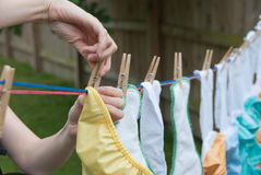 Cloth Diapers on a Clothesline. Laundry Day! A mom hangs cloth diapers on a clothesline to dry in the sun Royalty Free Stock Photography