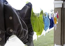 Cloth diapers hanging on clothes line. Colorful cloth diapers are hanging to dry Royalty Free Stock Images