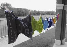 Cloth diapers hanging on clothes line. Colorful cloth diapers are hanging to dry on a clothes line. Background is in black and white while diapers are in color Stock Photography