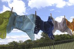 Cloth diapers hanging on clothes line. Five colorful cloth diapers are hanging to dry on a clothes line with blue sky Royalty Free Stock Photo