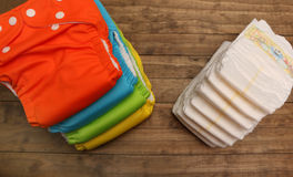 Cloth and Disposable Diapers. Stacks of cloth and disposable diapers on a wooded background Royalty Free Stock Image