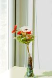 Cloth flower in glass jug on morning shine day. stock photo