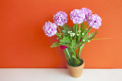 Cloth flowers, artificial decoration on orange wall stock photo