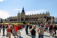 Cloth Hall (Sukiennice) in Cracow, Poland. CRACOW, POLAND - AUGUST 16, 2014: Tourists visiting the main market square in Cracow (Poland), which is one of the royalty free stock photo