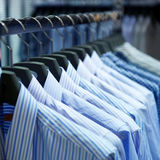 Cloth hangers with shirts. Row of cloth hangers with shirts Royalty Free Stock Photos