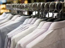Cloth hangers with shirts. Row of cloth hangers with shirts Royalty Free Stock Photo