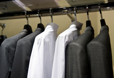 Cloth hangers with shirts. Row of cloth hangers with shirts and suit Royalty Free Stock Image