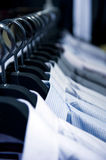 Cloth hangers with shirts. Row of cloth hangers with shirts Royalty Free Stock Images