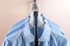 Cloth Hangers with Shirts. Men`s clothes. Clothes hang on a shelf . Cloth Hangers with Shirts. Men`s business clothes. Fashion Stock Image