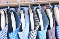 Cloth Hangers with Shirts. Men`s clothes. Clothes hang on a shelf . Cloth Hangers with Shirts. Men`s business clothes Stock Photo