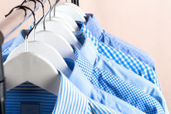 Cloth Hangers with Shirts. Men`s clothes. Clothes hang on a shelf . Cloth Hangers with Shirts. Men`s business clothes Stock Image
