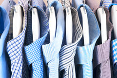 Cloth Hangers with Shirts. Men`s clothes. Clothes hang on a shelf . Cloth Hangers with Shirts. Men`s business clothes Stock Photography