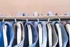 Cloth Hangers with Shirts. Men`s clothes. Clothes hang on a shelf . Cloth Hangers with Shirts. Men`s business clothes Royalty Free Stock Images