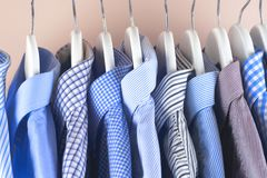 Cloth Hangers with Shirts. Men`s clothes. Clothes hang on a shelf . Cloth Hangers with Shirts. Men`s business clothes. Fashion Royalty Free Stock Photo