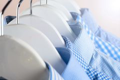Cloth Hangers with Shirts. Men`s clothes. Clothes hang on a shelf . Cloth Hangers with Shirts. Men`s business clothes. Fashion Stock Photo