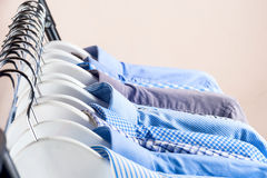 Cloth Hangers with Shirts. Men`s clothes. Clothes hang on a shelf . Cloth Hangers with Shirts. Men`s business clothes. Fashion Royalty Free Stock Photos