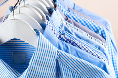 Cloth Hangers with Shirts. Men`s clothes. Clothes hang on a shelf . Cloth Hangers with Shirts. Men`s business clothes. Fashion Stock Photos