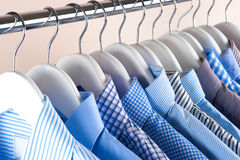 Cloth Hangers with Shirts. Men`s clothes. Clothes hang on a shelf . Cloth Hangers with Shirts. Men`s business clothes. Fashion Stock Images