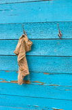 Cloth hanging on a hook. A wooden turquoise background Stock Photos