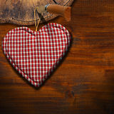 Cloth Heart on Brown Wood Background. Handmade clothe heart hanging on wooden background with trunk section Stock Photos
