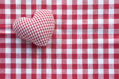 Cloth heart from checked pattern fabric on a red and white check. Cloth heart from small checked pattern fabric  in red and white on a background of a bigger Royalty Free Stock Image