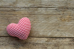 Cloth heart with red white pattern on rustic old wood Stock Photography