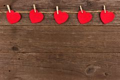 Cloth hearts on a line, top border against rustic wood. Cloth hearts hanging from line, top border against a rustic old wood background Stock Photos