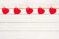 Cloth hearts on a line, top border against white wood. Cloth hearts hanging from a line, top border against a rustic white wood background Stock Photography