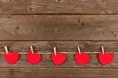 Cloth hearts on a line, bottom border against rustic wood. Cloth hearts hanging from line, bottom border against a rustic old wood background Stock Image