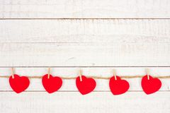 Cloth hearts on a line, bottom border against white wood. Cloth hearts hanging from a line, bottom border against a rustic white wood background Royalty Free Stock Photos