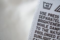 Cloth label tag with laundry care instructions. Close up stock photo