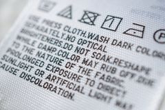 Cloth label tag with laundry care instructions. Close up royalty free stock photo